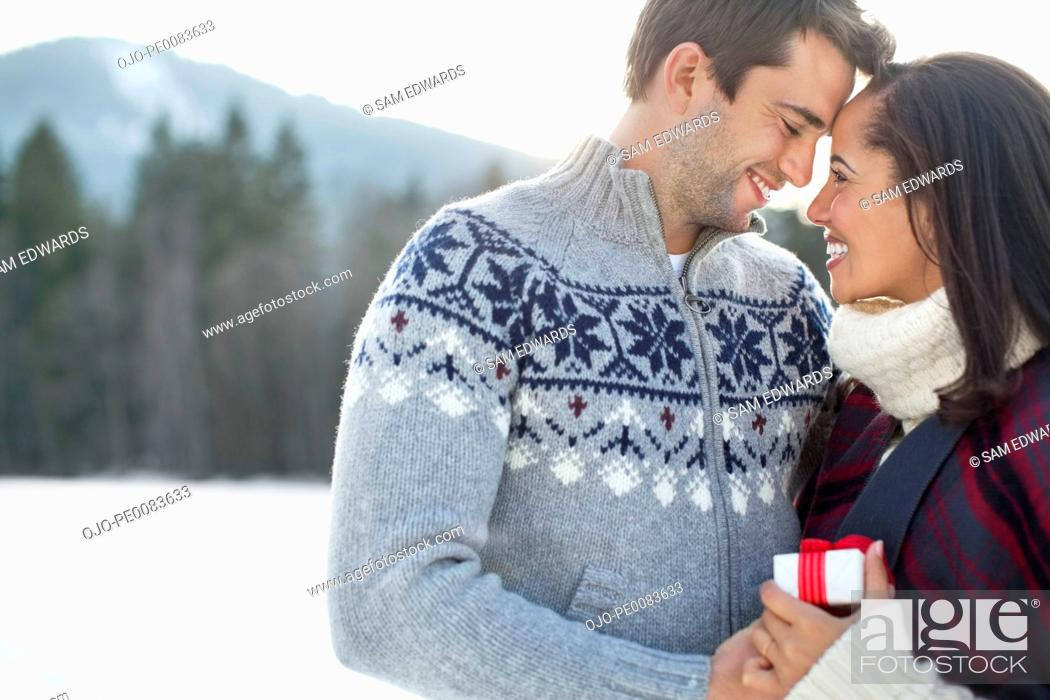 Stock Photo: Smiling couple face to face in snowy field.