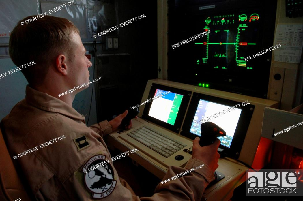 Stock Photo: An Air Force officer maneuvers an unmanned Predator reconnaissance airplane over Iraq by remote control at Balad Air Base.
