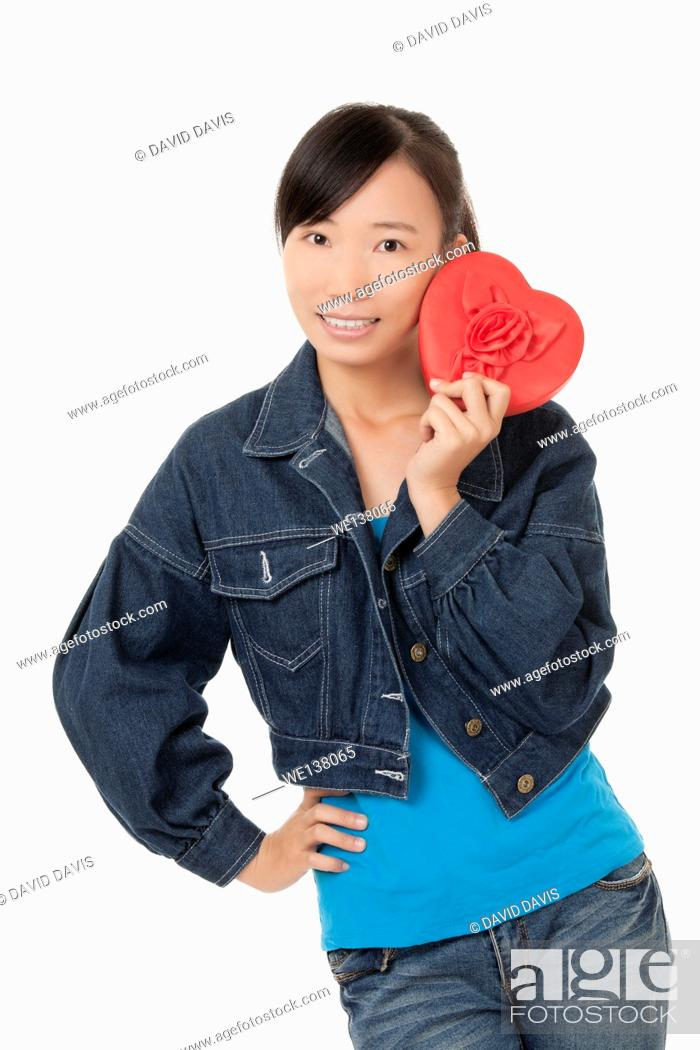 Stock Photo: Beautiful Chinese woman holding a red heart and flirting with someone isolated on a white background.