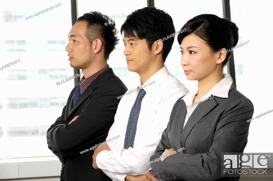 Stock Photo: Business executives standing in a row in an office.