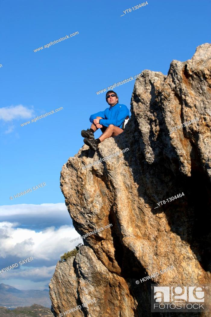 Stock Photo: Man sitting on a rock ledge.