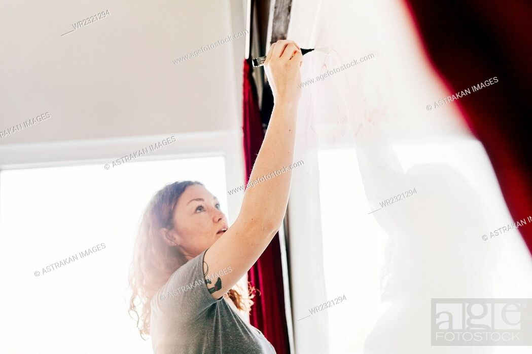 Stock Photo: Low angle view of businesswoman writing on whiteboard in office.