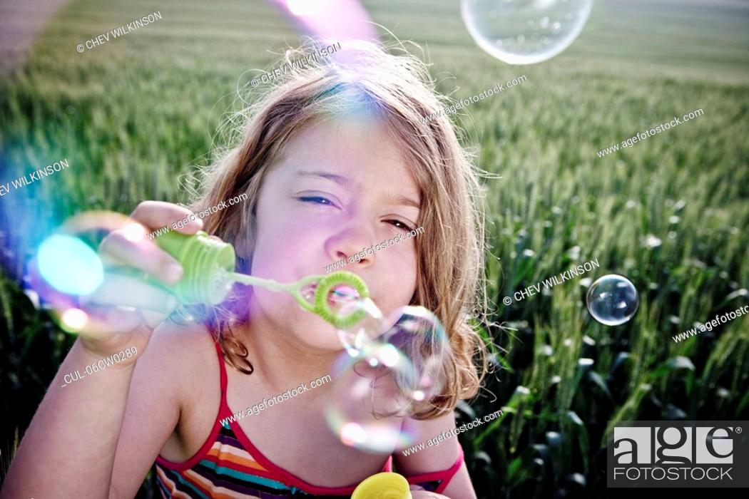 Stock Photo: Girl blowing bubbles to camera.