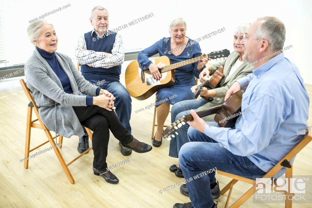 Imagen: Seniors in retirement home attending guitar class, making music.
