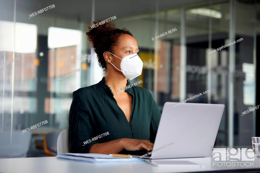 Stock Photo: Portrait of businesswoman wearing protective mask working on laptop at counter looking at distance.