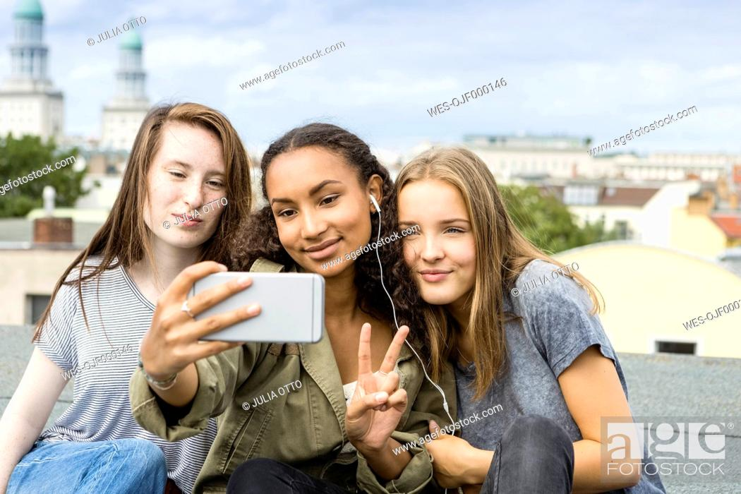 Stock Photo: Germany, Berlin, three teenage girls sitting on roof top taking selfie with smartphone.