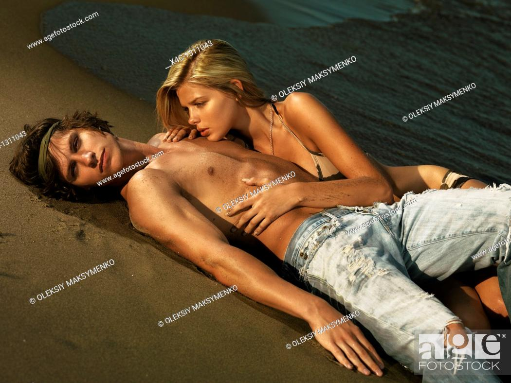 Stock Photo: Young woman in bkini and a young man in jeans lying on the shore.