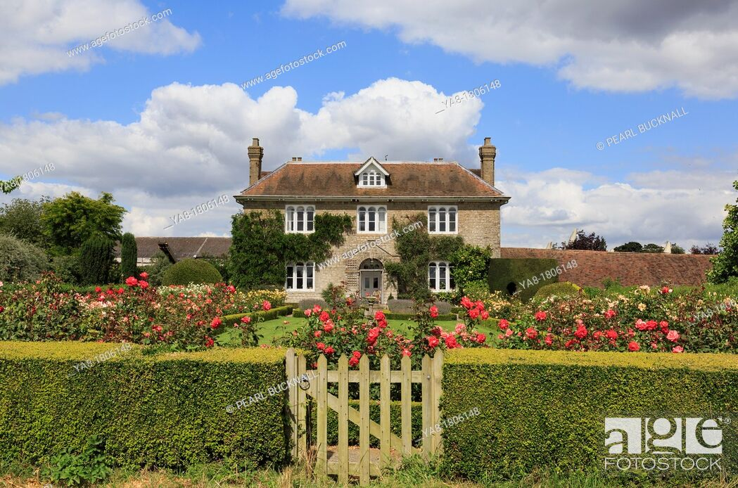 Stock Photo: Pluckley, Ashford, Kent, England, UK, Britain, Europe  Hedge with gate to rose garden in front of an English country house 1816 in summer.