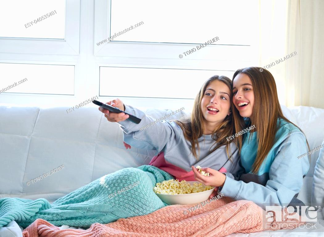 Stock Photo: best friend girls watching TV cinema at home with popcorn.