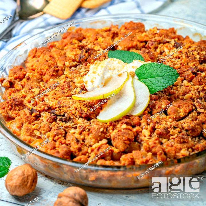 Stock Photo: Pie crumble with pear, cinnamon, walnuts and natural yogurt in a glass baking dish on a white wooden table, selective focus. Square image.