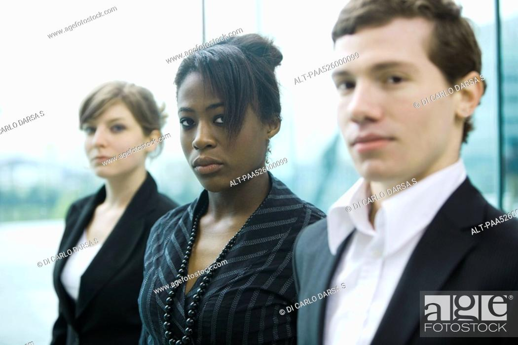 Stock Photo: Three business associates standing side by side looking at camera.