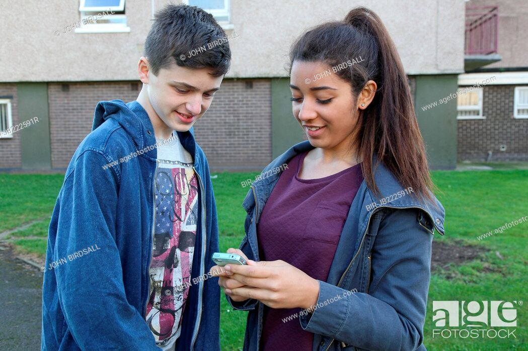 Imagen: Teenage girl and boy looking at mobile phone.