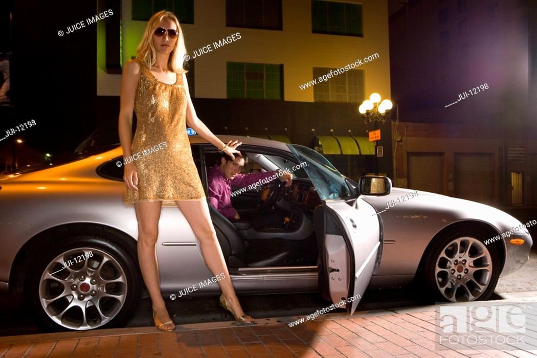 Stock Photo: Young woman by open door of car, low angle view, night.