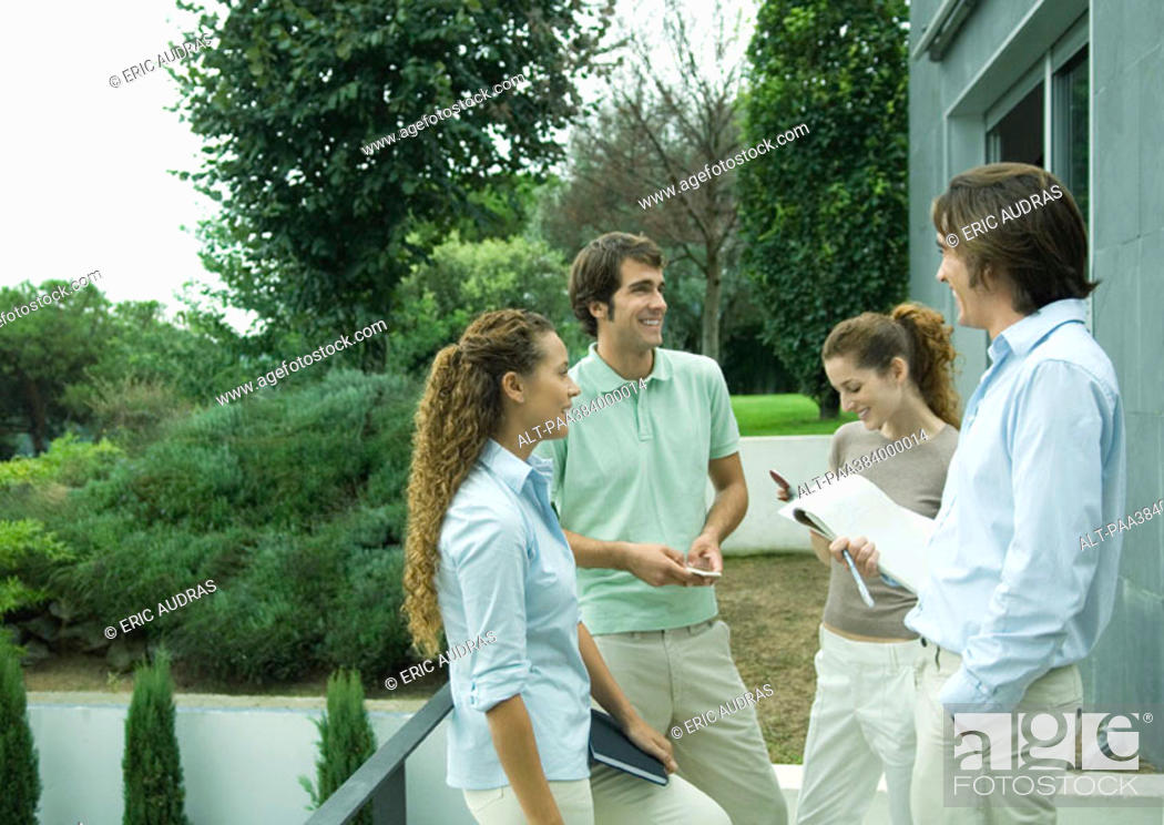Stock Photo: Casually dressed young executives standing outdoors, talking.