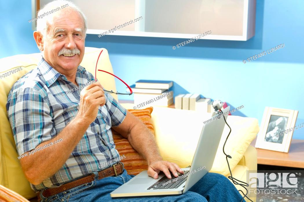 Stock Photo: Smiling senior man working at home.