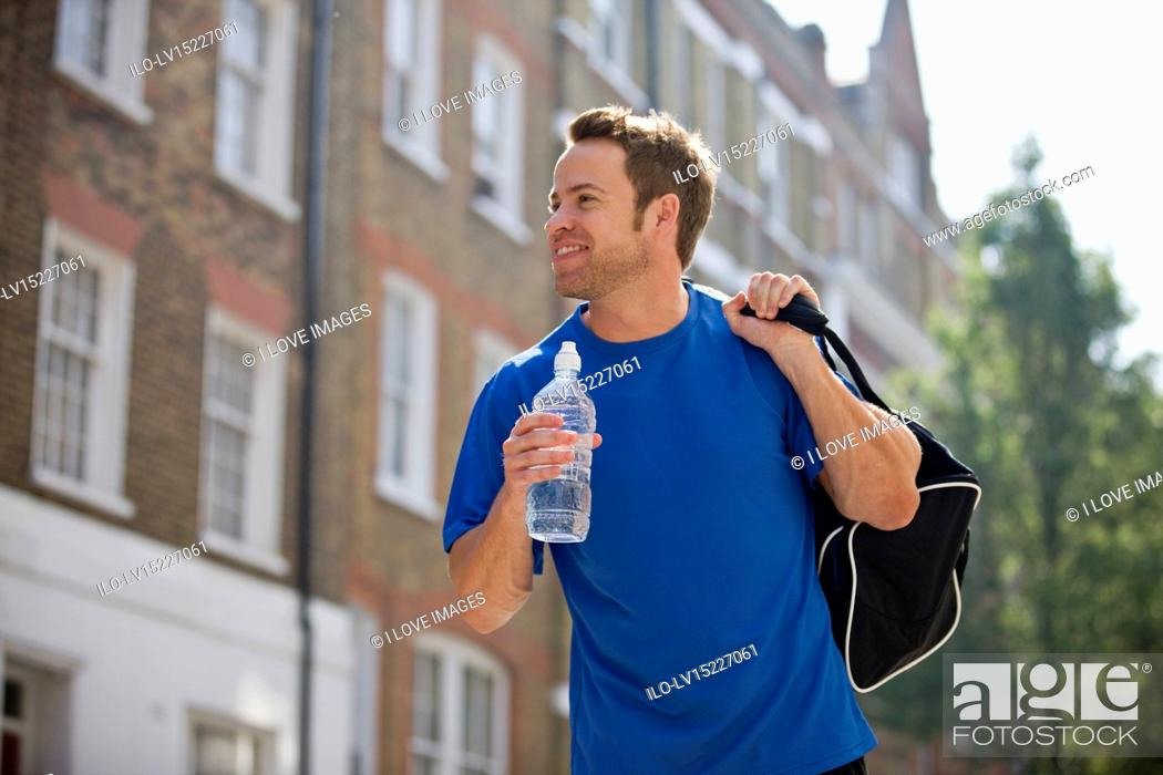 Stock Photo: A young man walking down the street, carrying a sports bag and a bottle of water.