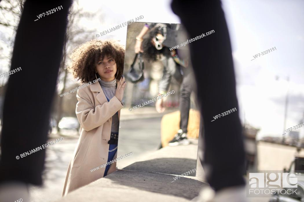 Stock Photo: young woman holding mirror reflecting fashionable man, in Paris, France.