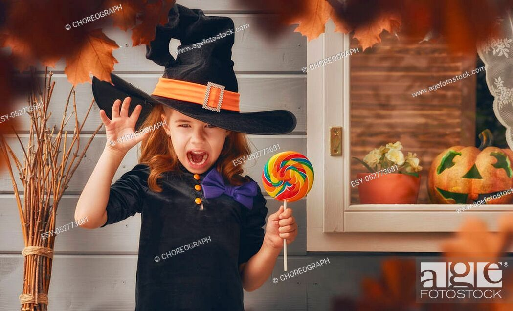 Stock Photo: Happy Halloween! Cute cheerful little witch outdoors. Beautiful child girl in witch costume near house decorated to Halloween.