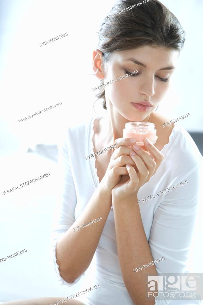 Stock Photo: young woman holding cream.
