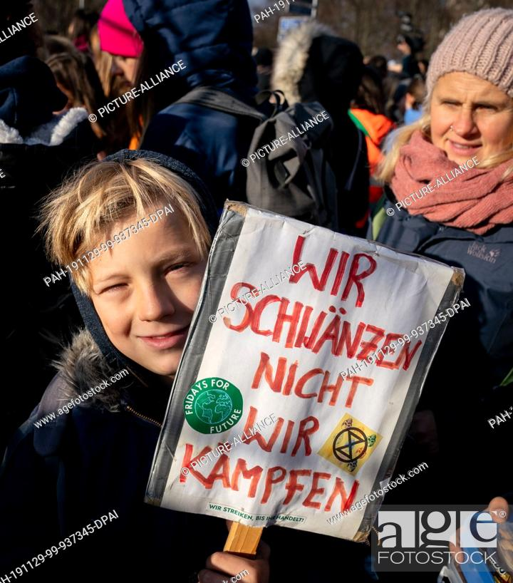 Stock Photo: 29 November 2019, Berlin: Young people take part in the rally of Fridays For Future at the Brandenburg Gate. From 2 to 13 December 2019.