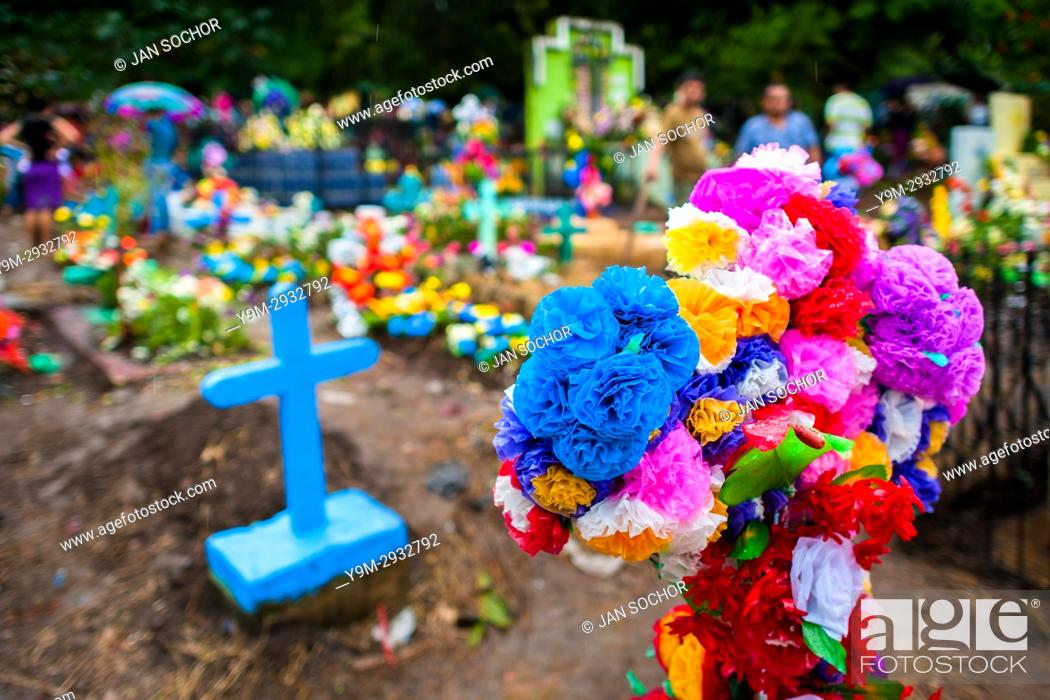 A graves cross decorated with colorful paper flowers is seen stock photo a graves cross decorated with colorful paper flowers is seen during the day of the dead celebration at the cemetery in izalco el salvador mightylinksfo