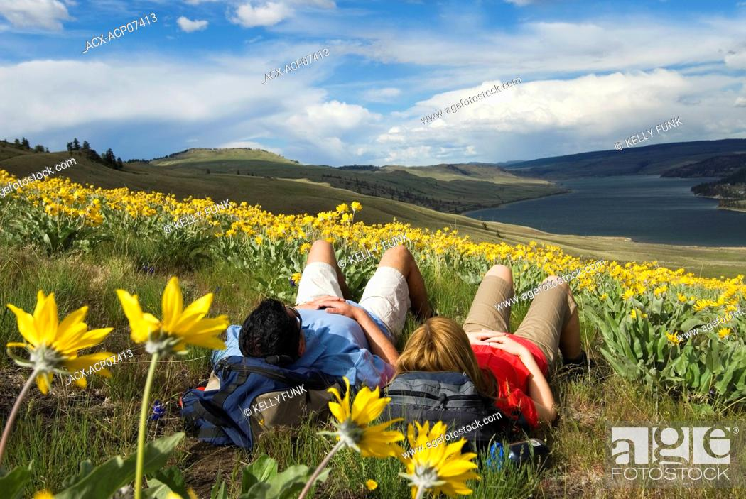 Imagen: A young couple takes a break from hiking in the wildflowers above Stump Lake, just South of Kamloops, British Columbia, Canada.