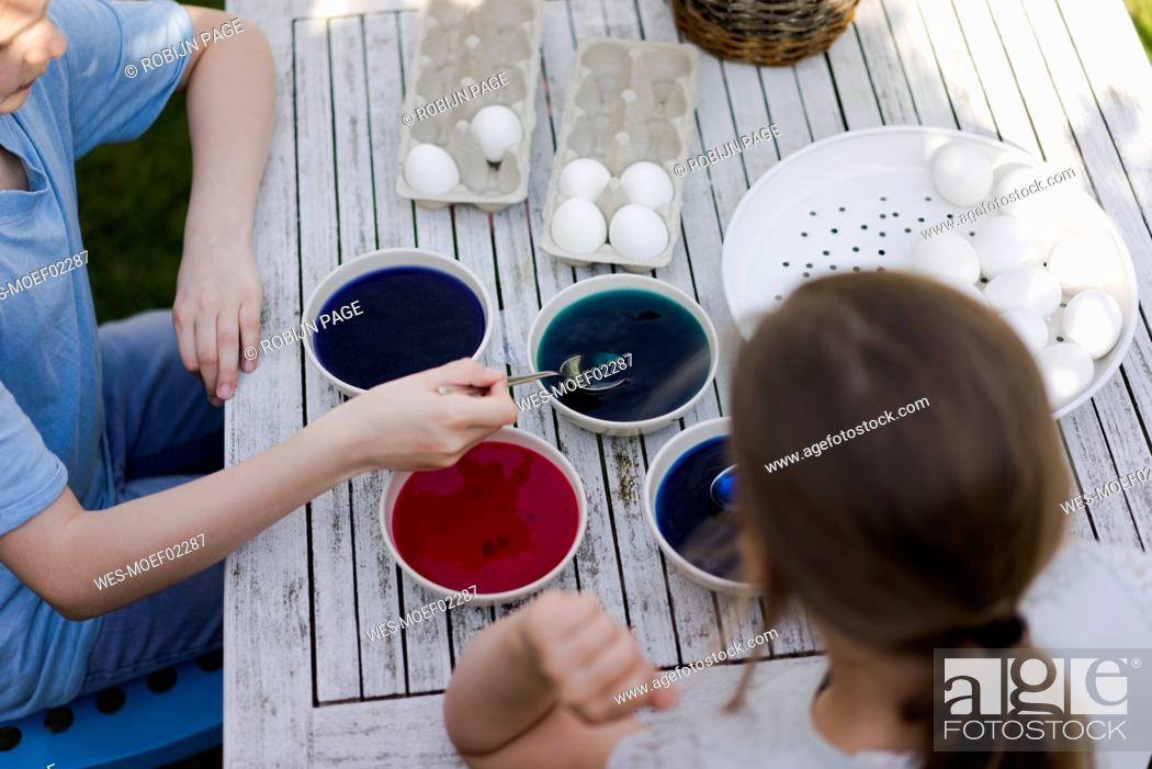 Stock Photo: Two girls dyeing Easter eggs on garden table.