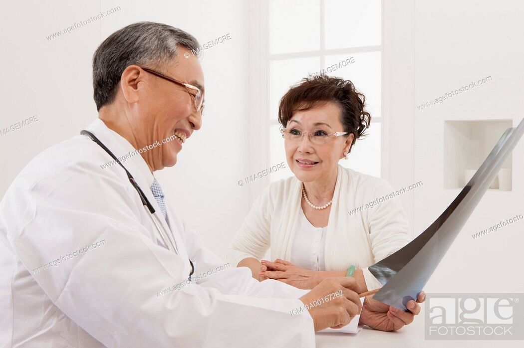 Stock Photo: Senior woman making medical exam and looking away with smile.