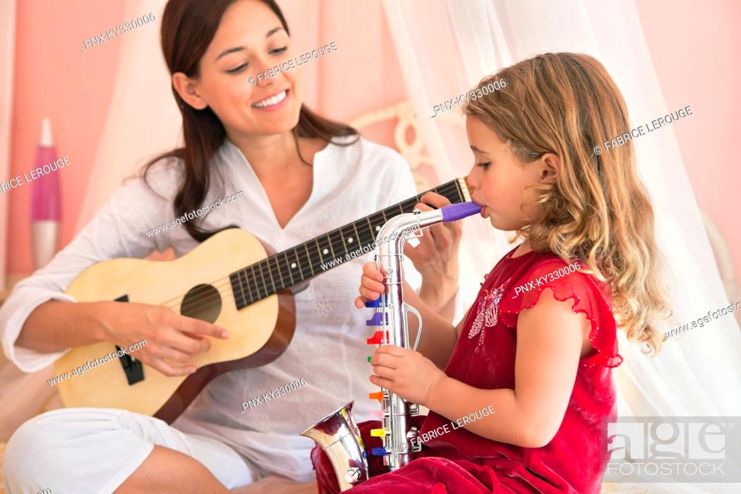 Stock Photo: Woman playing guitar with her daughter playing saxophone.
