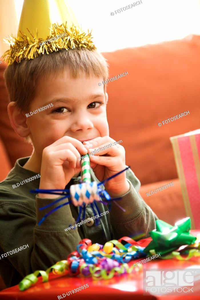 Stock Photo: Caucasian boy at birthday party looking at viewer blowing noisemaker.