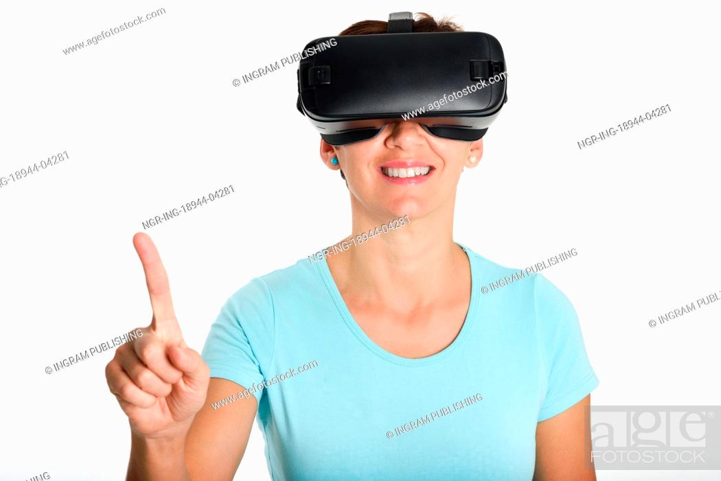 Imagen: Woman looking in VR glasses and gesturing with his hands. Beautiful surprised female wearing virtual reality goggles watching movies or playing video games.