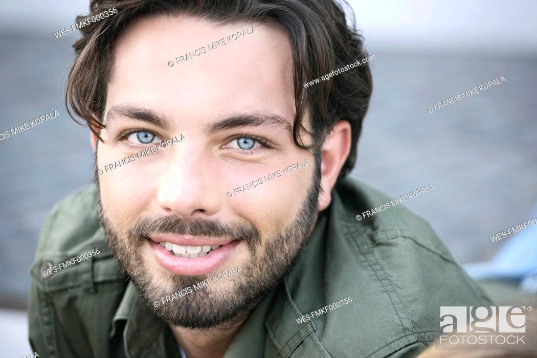 Stock Photo: Germany, Cologne, Young man smiling, portrait.
