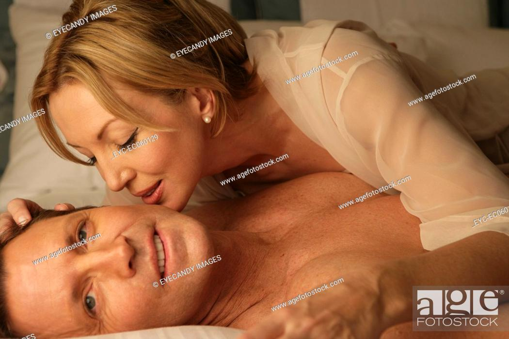 Stock Photo: Mature couple in bed kissing.
