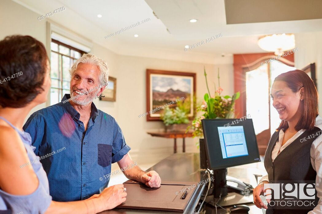 Stock Photo: Mature couple checking in at hotel reception.