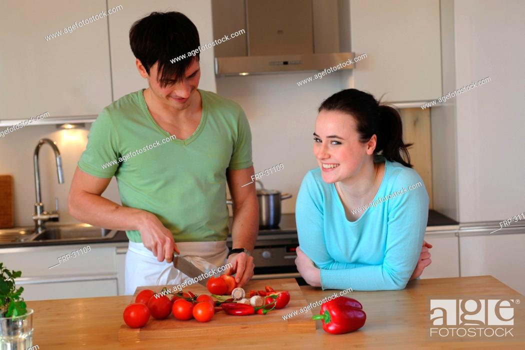 Stock Photo: Young couple in kitchen slicing vegetables.