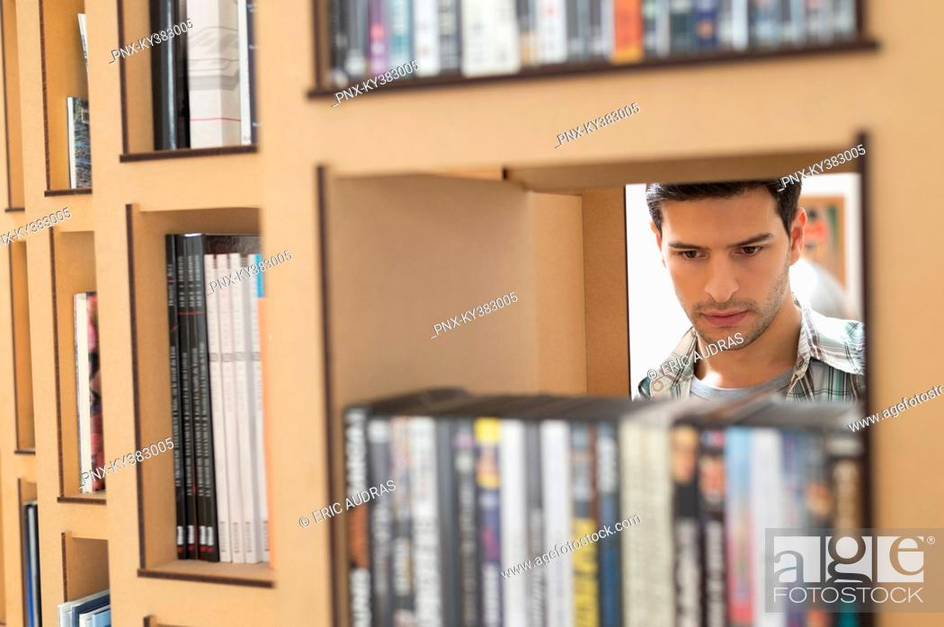 Stock Photo: Man choosing books from a bookshelf.