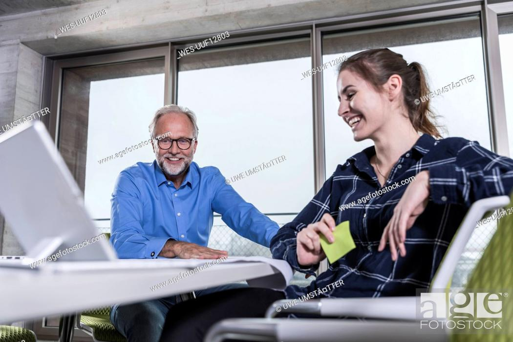 Imagen: Smiling mature businessman and young woman with tablet in conference room in office.