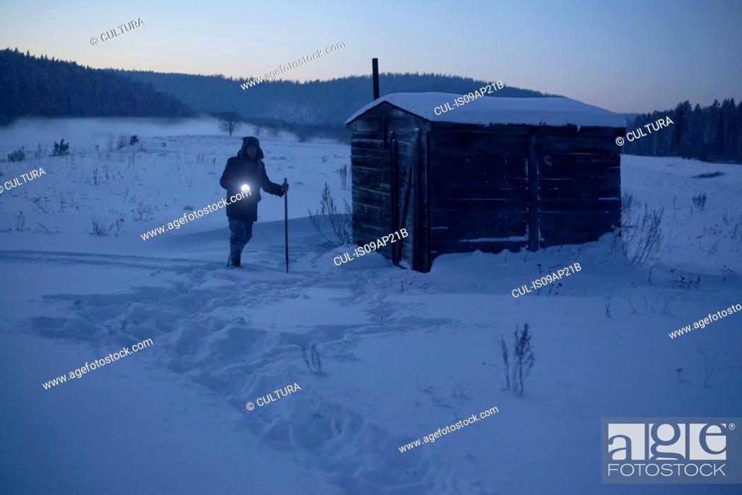 Photo de stock: Man in snow covered landscape pointing torch at dusk, Sarsy village, Sverdlovsk Oblast, Russia.
