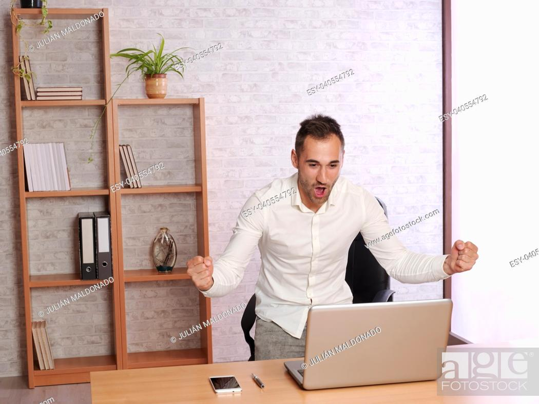 Stock Photo: Young man at home celebrating a goal from his team.