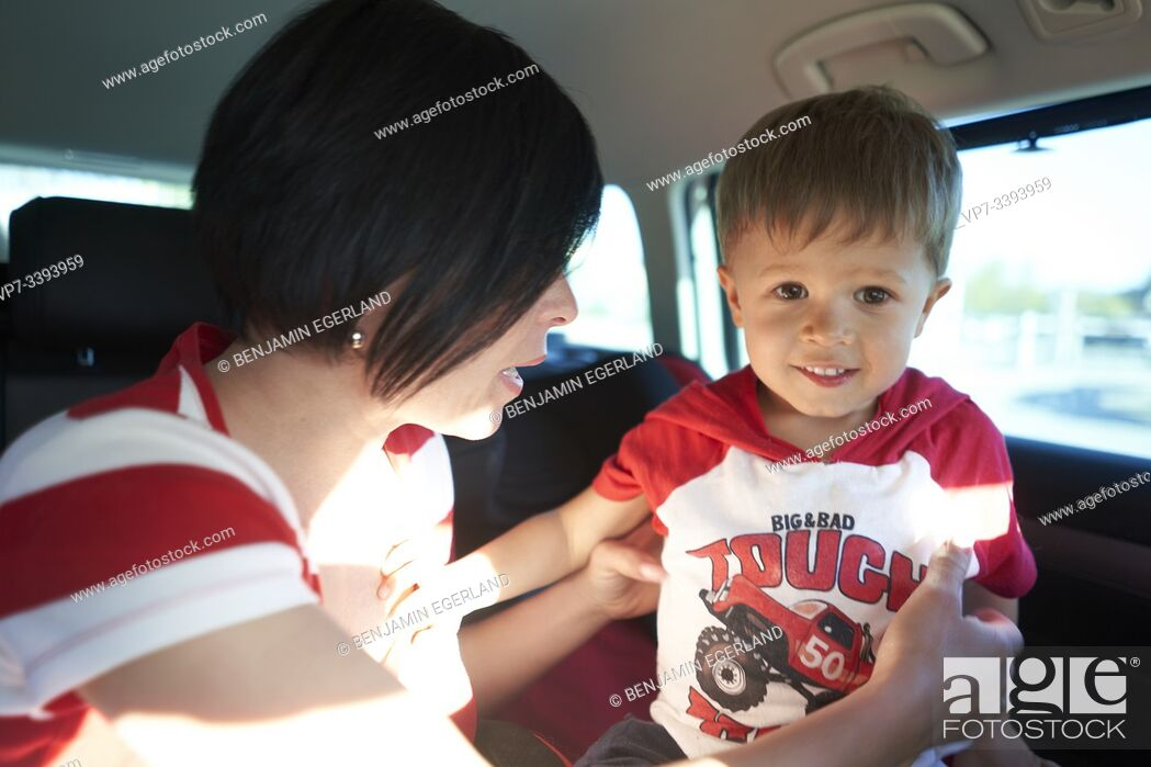 Photo de stock: mother guiding son to sit down in baby seat inside car, toddler child.