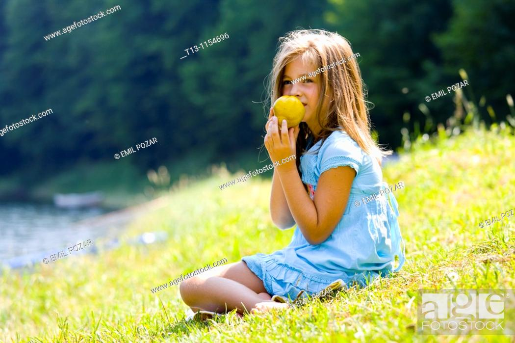 Stock Photo: Six year old girl is eating a pear.