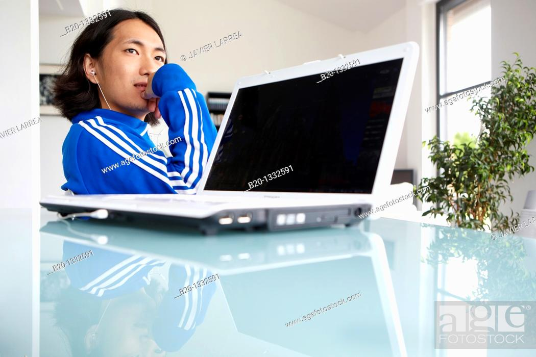 Stock Photo: Young Japanese man with laptop computer in room.