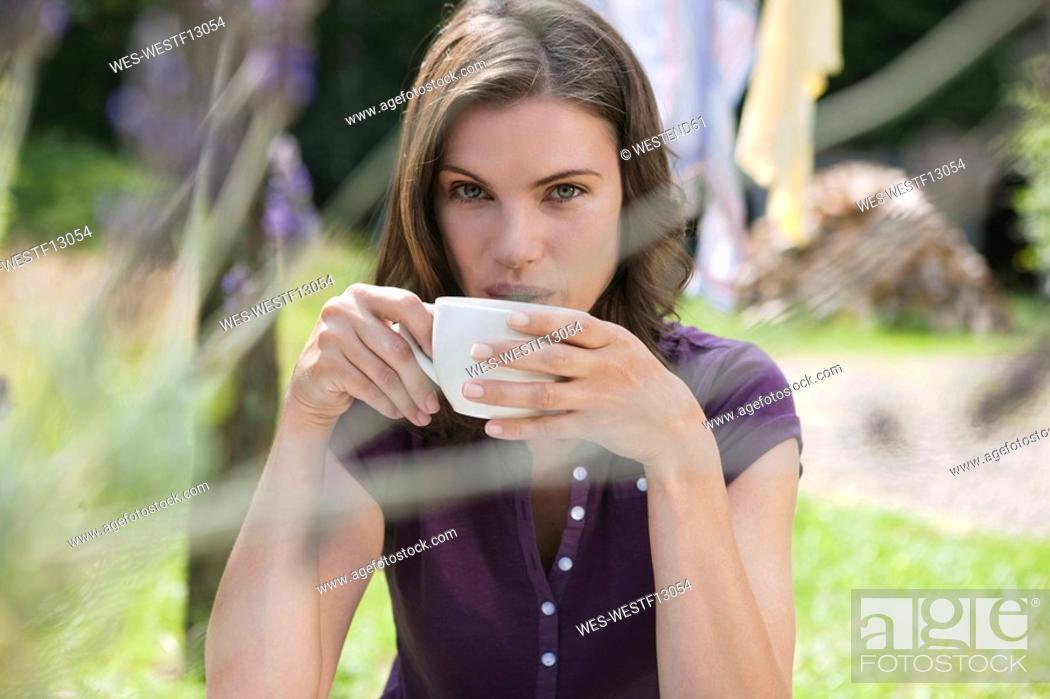 Stock Photo: Germany, Hamburg, Woman in garden holding cup of coffee.