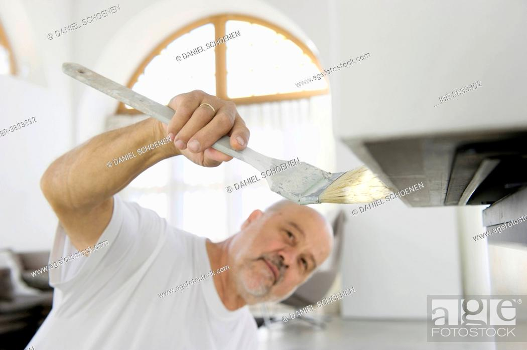 Stock Photo: Elderly craftsman painting a surface.