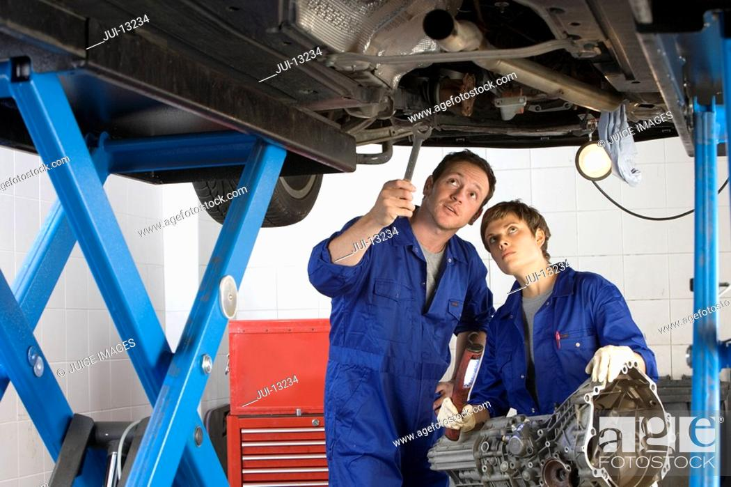 Stock Photo: Mechanic and colleague beneath elevated car, pointing with wrench.