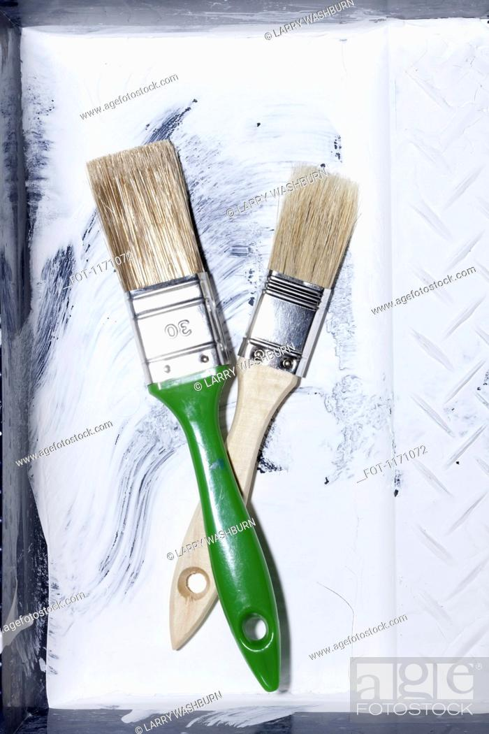 Stock Photo: Two new house painting brushes crossing each other and lying in an old paint tray.