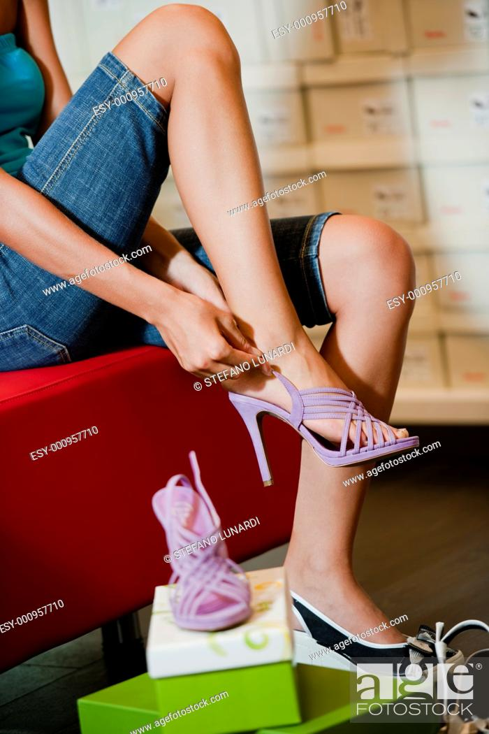 Stock Photo: Young woman trying shoes on.