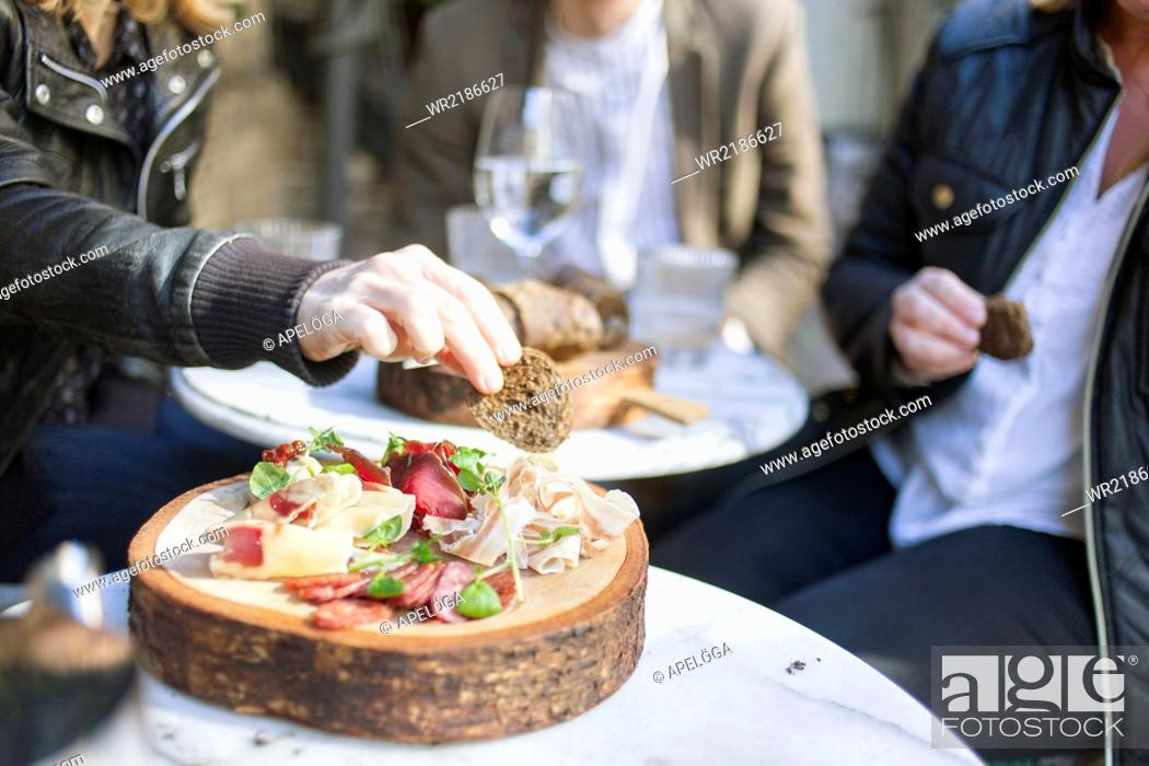 Stock Photo: Midsection of people having breads at outdoor restaurant.