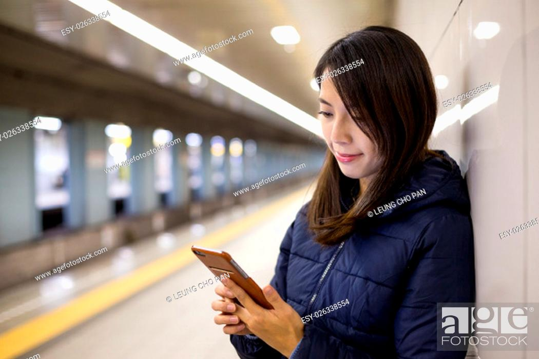 Stock Photo: Woman using mobile phone in metro station.