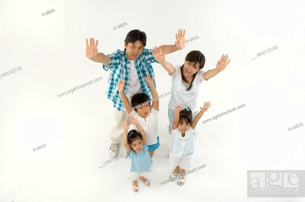 Stock Photo: Family standing with arms raised.
